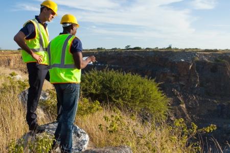 deux arpenteurs hommes travaillant au site minier
