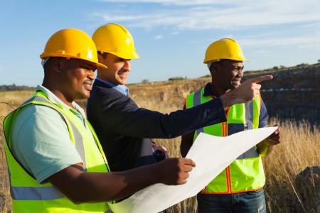 topografo: gerente y los trabajadores de la mina en la cantera de discutir planes futuros