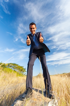 cheerful young businessman on top of rock giving thumbs up outdoors Stock Photo - 20022606