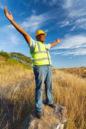 blue collar: excited african construction worker with arms outstretched outdoors Stock Photo