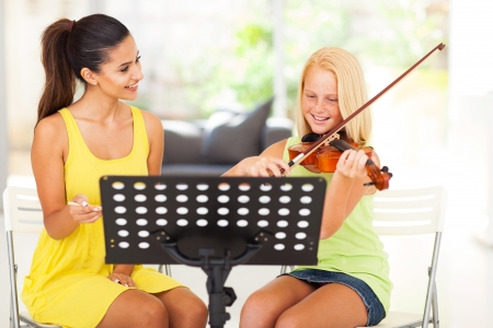 woman violin: beautiful music teacher tutoring young girl to play violin