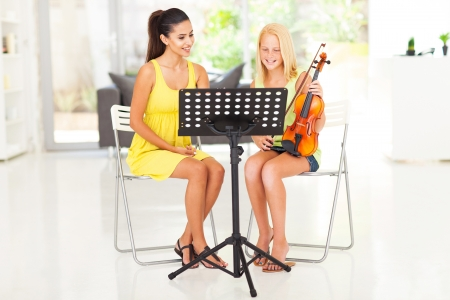 tutoring: beautiful young pretty girl having violin lesson at home
