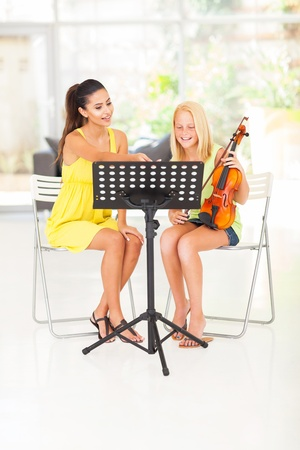 preteen girl having violin lesson with her teacher at home photo