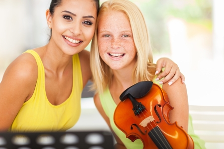 beautiful female music teacher with violin student photo