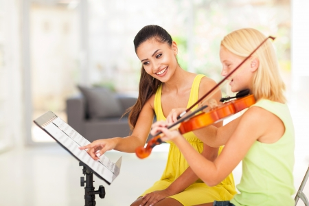tutoring: preteen girl play violin under music teachers instructions