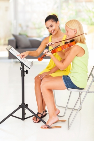 teaching music: smiling music teacher pointing notes for violin student Stock Photo