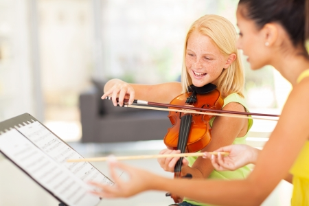 violins: beautiful preteen girl in music class with music teacher