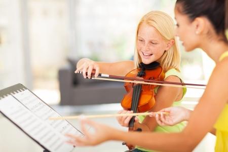 violines: hermosa niña preadolescente en la clase de música con el profesor de música