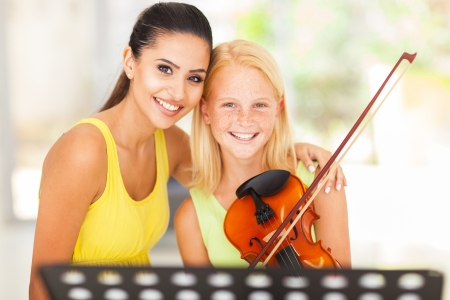 beautiful music teacher with young violin student Stock Photo