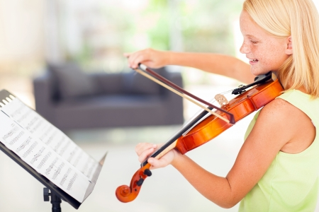freckled: cheerful talented preteen girl playing violin at home