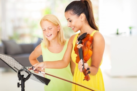 tutoring: pretty music teacher pointing notes to her student Stock Photo