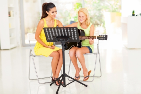 happy preteen girl having guitar lesson with music tutor at home photo