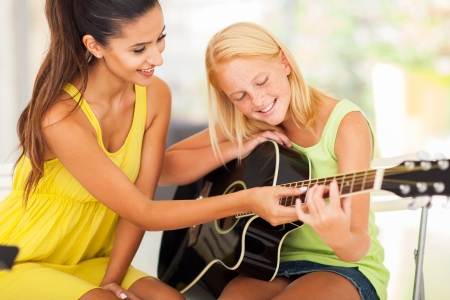 pre adult: smiling beautiful music teacher tutoring young girl to play guitar