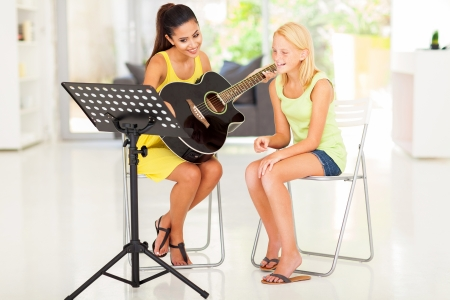 teaching music: beautiful young preteen girl having guitar lesson at home