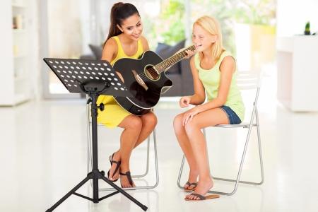 beautiful teacher: beautiful young preteen girl having guitar lesson at home