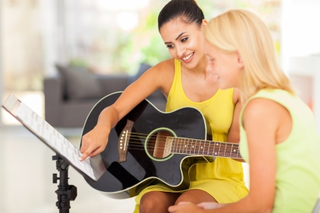 pretty music teacher tutoring young girl to play guitar photo