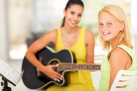 happy pre teen girl in music class with teacher photo