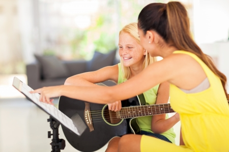 teaching music: young preteen girl having guitar lesson at home Stock Photo