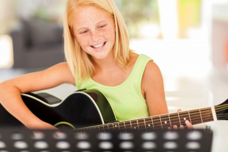 girl playing guitar: cheerful young pre teen musician playing guitar