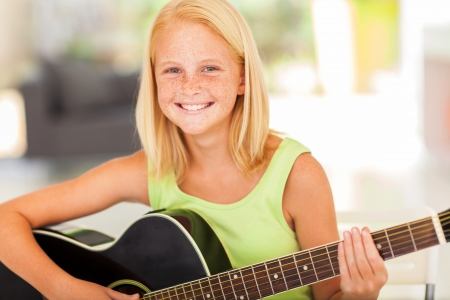 girl playing guitar: happy pre teen girl practicing  guitar at home
