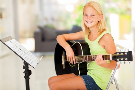 girl playing guitar: cheerful preteen girl practicing guitar at home