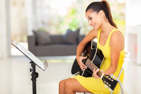 girl playing guitar: smiling pretty young woman playing guitar at home