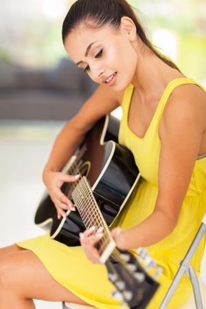 lekce: krásná žena hraje na kytaru doma