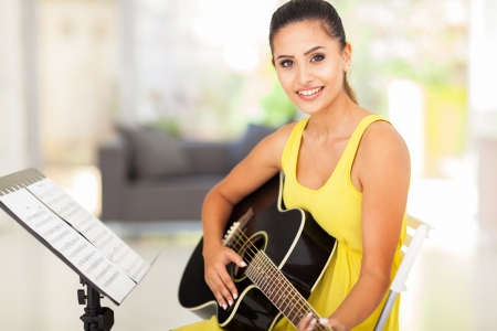 guitarists: cute young woman practicing guitar at home