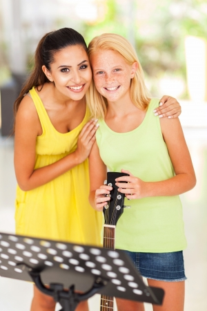 cheerful music teacher with preteen girl after music lesson photo
