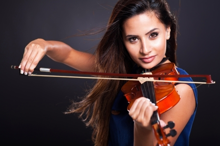 attractive young woman playing violin on black background photo