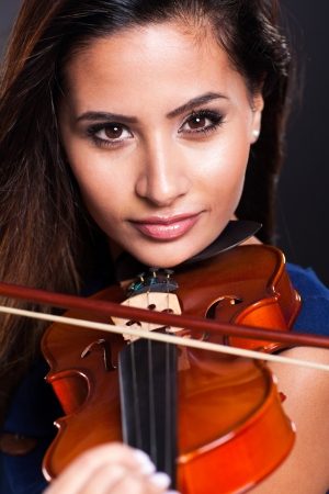 portrait of beautiful violinist over black background photo