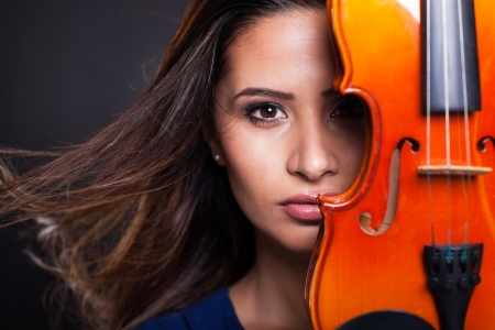portrait of pretty woman behind a violin on black background photo