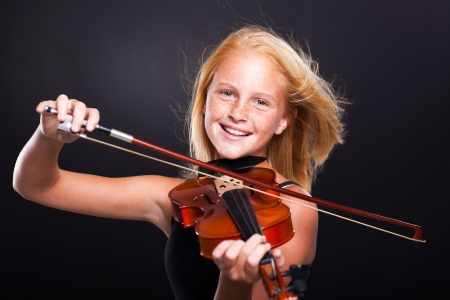 cheerful preteen girl playing violin on black background