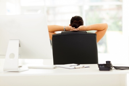 rear view of businesswoman relaxing in office with both hands behind her head photo