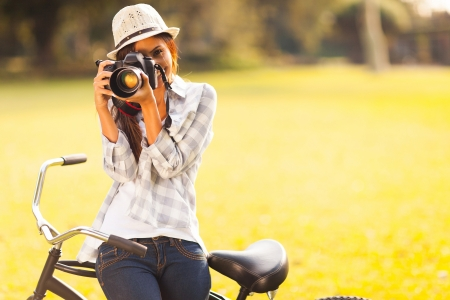 photographer: smiling young woman using a camera to take photo outdoors at the park
