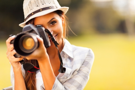 to  camera: attractive young woman talking pictures outdoors
