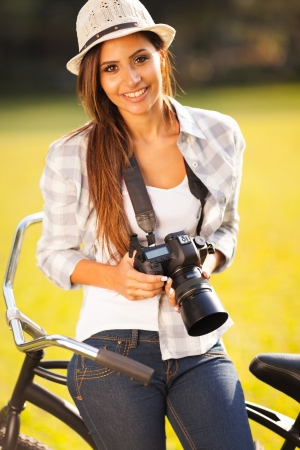 pretty woman with camera sitting on bicycle outdoors photo