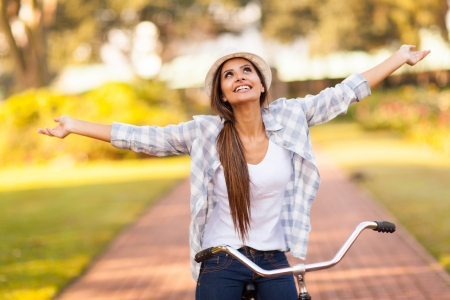 glädje: vacker ung kvinna njuter ridning cykel i parken med utsträckta armar Stockfoto