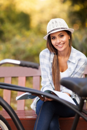 recreational vehicle: young woman sitting on bench in park reading book, smiling and looking into the camera