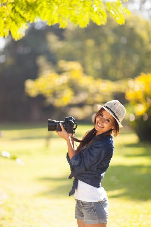 cheerful young photography student take photos outdoors at the park photo