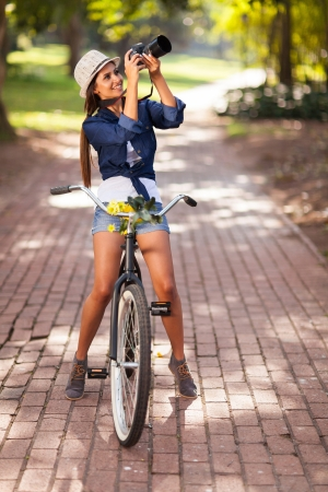 photographers: attractive young woman taking pictures on her bike outdoors