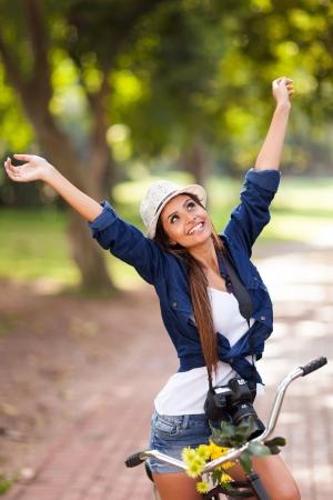 zorgeloze jonge vrouw open armen op haar fiets buiten Stockfoto