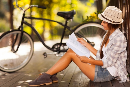 girl on bike: beautiful young woman studying at the park