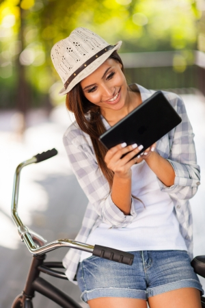 spring hat: cheerful young woman using tablet computer outdoors