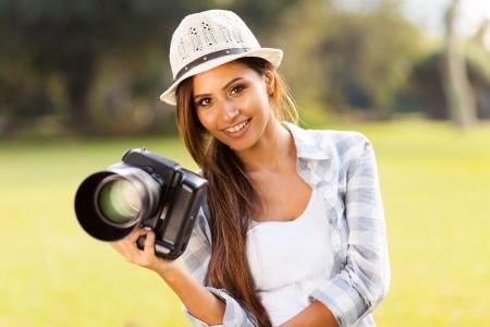 屋外カメラを保持している魅力的な女の子の肖像画