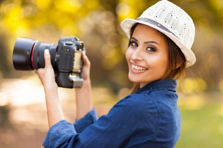 smiling young woman learning to use camera outdoors