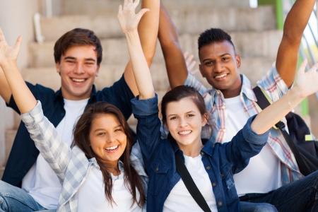 high school students: estudiantes emocionados de secundaria con los brazos extendidos al aire libre