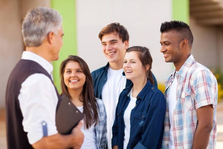 middle aged high school teacher talking to students during break photo