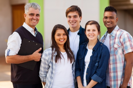 cheerful male high school teacher standing with students outdoors photo
