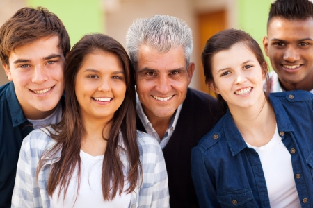 close up portrait of cheerful high school teacher and teenage students photo